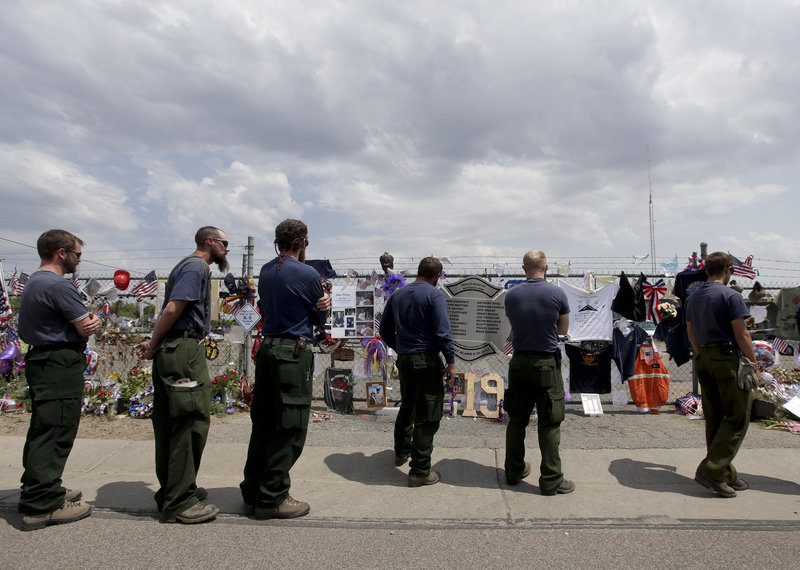 Fire crew members from Island Park, Idaho, pay their respects Thursday at a memorial in Prescott, Ariz., to the 19 firefighters killed Sunday.
