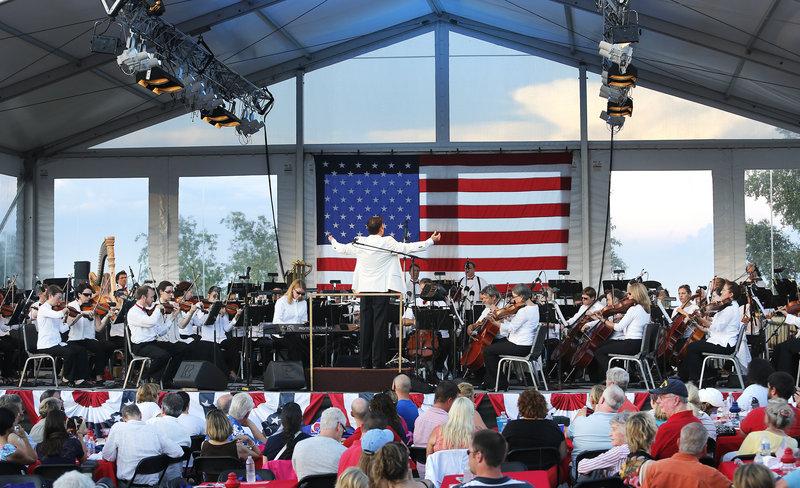 Maestro Robert Moody conducts the Portland Symphony Orchestra on the covered stage on Cutter Street. The PSO performed superhero-themed popular music and patriotic standards.
