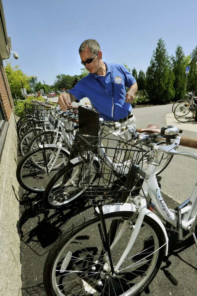 Brian Beeler II, manager of passenger services for the Downeaster, demonstrates how to unlock one of the bicycles being offered for rent at the Portland Transportation Center. Bikes can be rented for $20 a day under the program, which is targeted at tourists coming up for the day from Boston.