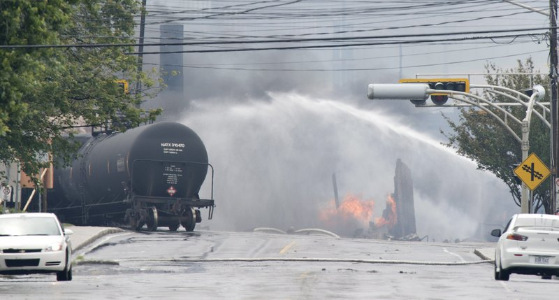 Smoke and fire rise from railway cars that were carrying crude oil after derailing in downtown Lac Megantic, Que., Saturday, July 6, 2013. A large swath of Lac Megantic was destroyed Saturday after a train carrying crude oil derailed, sparking several explosions and forcing the evacuation of up to 1,000 people. (AP Photo/The Canadian Press, Paul Chiasson)