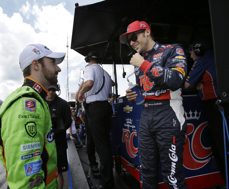 Marco Andretti, right, talks with teammate James Hinchcliffe after winning the pole for Sunday's IndyCar race at Pocono Raceway. Hinchcliffe qualified third.