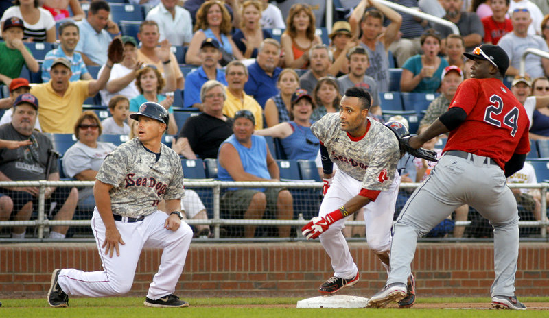Sea Dogs base runner Tony Thomas looks toward the plate, along with Manager John Boles and New Britain third baseman Miguel Sano, to see if he can score after an errant throw. Thomas held at third but eventually scored on a passed ball.