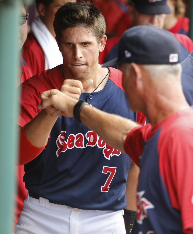 Garin Cecchini is met by Portland hitting coach Bob Kipper after doubling and scoring in the sixth inning Sunday.