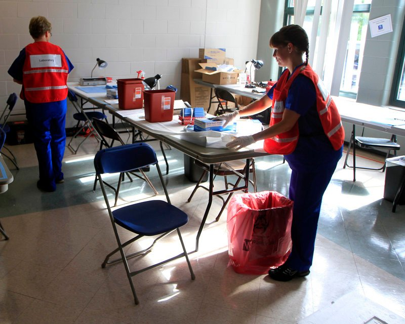 Laboratory scientists set up a lab in a middle school in Stratham, N.H., in this Aug. 11, 2012 file photo. Scientists were testing people for hepatitis C related to an outbreak at the Exeter Hospital allegedly caused by medical technician David Kwiatkowski.