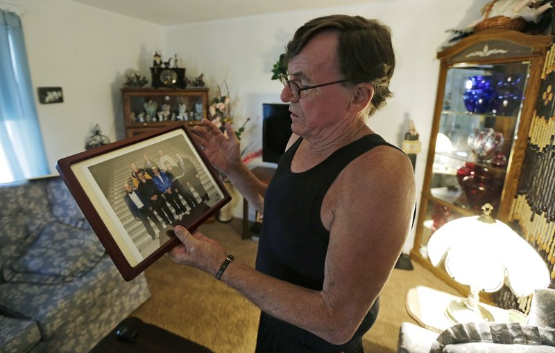 Charlie Dyer looks at a photograph of his school buddies from the Fernald State School at his home in Watertown, Mass. Dyer and his friends were essentially used as human guinea pigs.