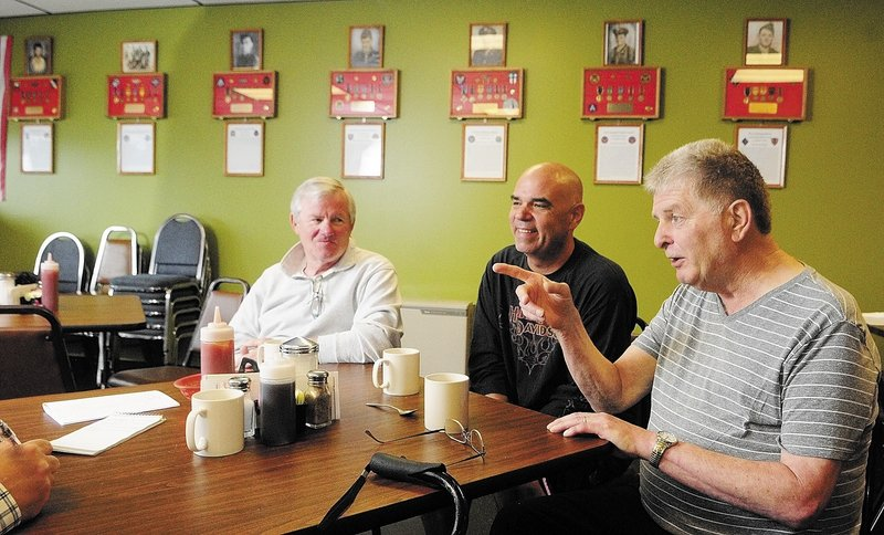 """David Harville, left, Thomas """"T.J."""" Quinn, center, and Larry Day talk about the memorial wall display last week at Quinn's restaurant, TJ's Place, in Monmouth. There are seven plaques on the wall, one for each of the soldiers from the town killed in action in World War II."""