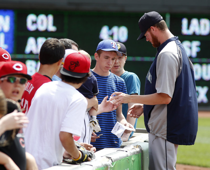 Mariners reliever Charlie Furbush of South Portland signs an autograph before Seattle's game with the Reds at Cincinnati on Sunday.