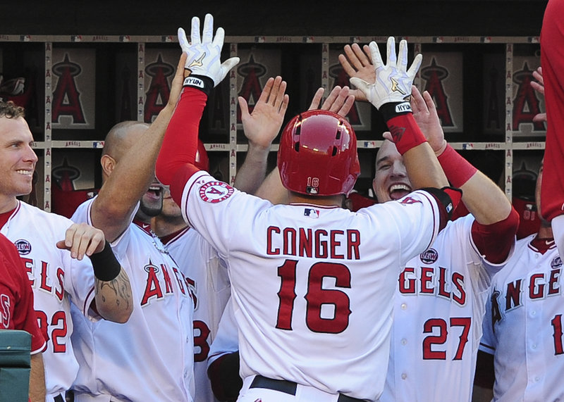 Hank Conger is greeted in the dugout by Mike Trout (27) and other teammates after his home run in the fifth inning gave the Angels a 2-0 lead. Trout also homered for the second straight game, helping the Angels to a 3-0 victory.