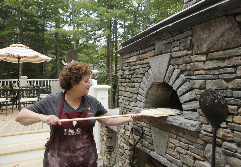 Instructor Jill Strauss shovels a Crabby Cheddar pizza into the oven, where the heat registered over 750 degrees, at Jillyanna's Woodfired Cooking School in Kennebunkport.