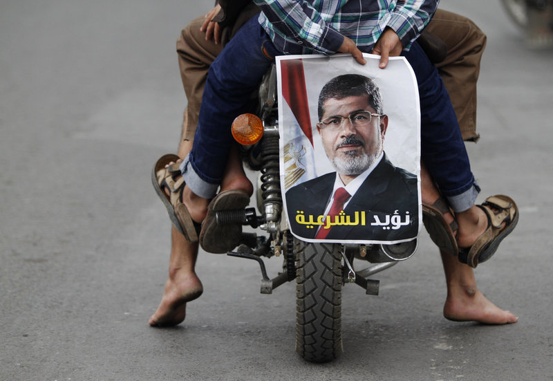 A pro-democracy protester holds a photo of deposed Egyptian President Mohamed Mursi while riding a motorcycle during a demonstration in Sanaa.