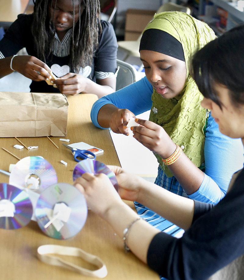 Lona Peter, 15, from Casco Bay High School, upper left, Sahra Ahmed, 14, Deering High School, middle, and Nilab Nasrat, 19, from Portland High School, build a mousetrap car at the Real School on Mackworth Island in Falmouth on July 10, 2013. A group of 16 girls are wrapping up a free, three-week STEM (science, technology, engineering, math) program, working with local companies to solve