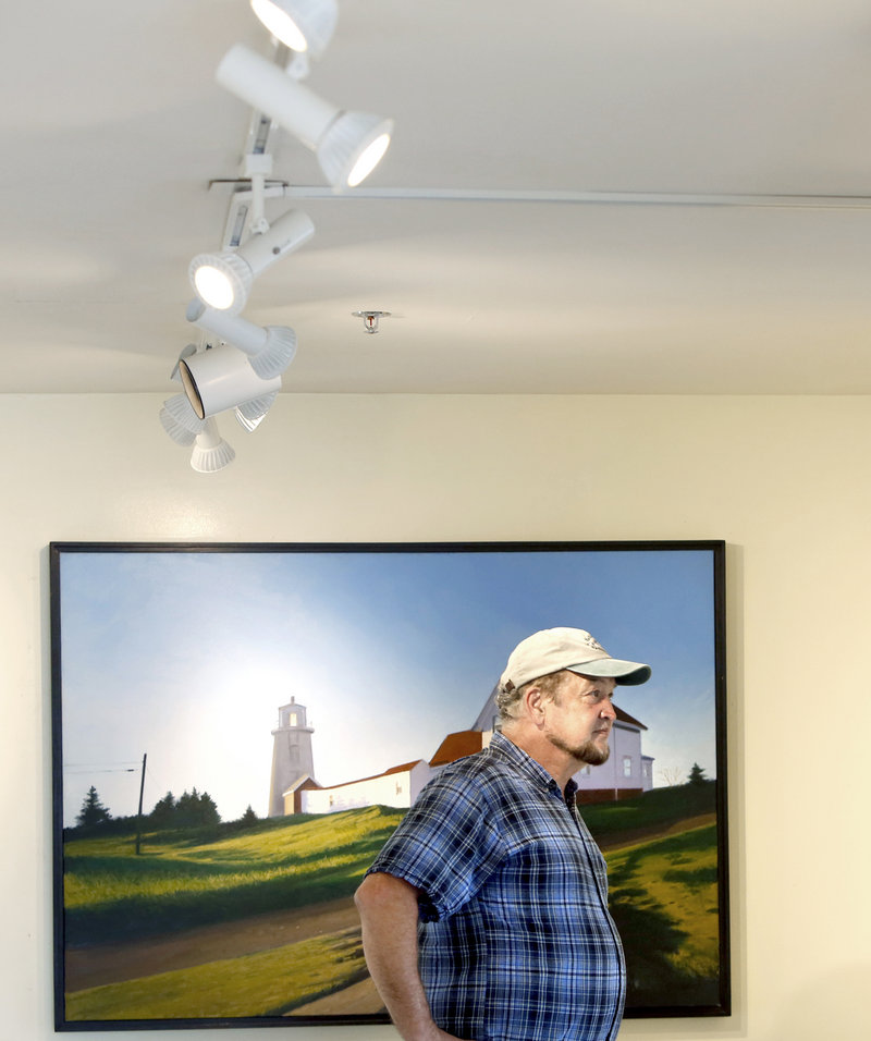 Michael Mayhew of Heliotropic Technologies looks over paintings at Gleason Fine Art in Boothbay Harbor. His company installed high-efficiency light bulbs at Gleason Fine Art and other businesses to reduce energy use.