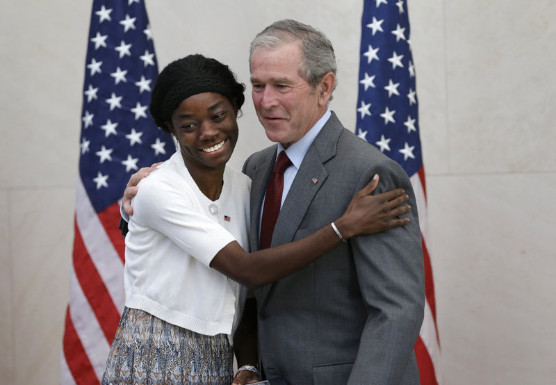 Former President George W. Bush poses with Mondell Bernadette Avril after she was sworn in as a U.S. citizen during a ceremony at the George W. Bush Institute in Dallas on Wednesday. The immigration system is broken, Bush said.