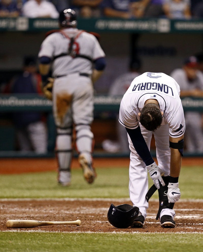 Tampa Bay's Evan Longoria takes off his ankle guard after striking out against the Twins on Wednesday night. Tampa Bay won 4-3 in 13 innings.