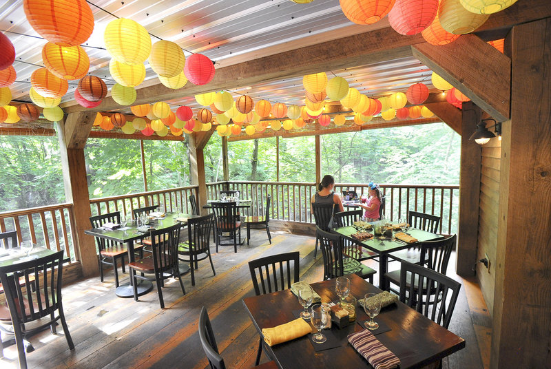The back porch dining area at Krista's offers a lush, tree-lined river view.