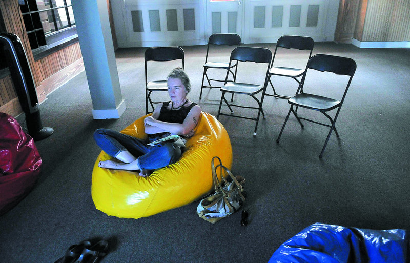 """Karen Young watches MIFFOnEdge's presentation of Nam Jun Paik's """"Global Groove,"""" a video made in the 1970s, from a beanbag chair at the old post office in downtown Waterville on Saturday."""