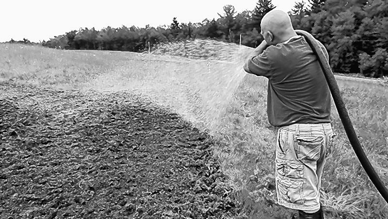 Norm Vigue of Central Maine Hydroseeding sprays a cover of wood fiber mulch, fertilizer and water onto the ground to protect newly planted wildflower seeds and help them grow at the Oakland transfer station.