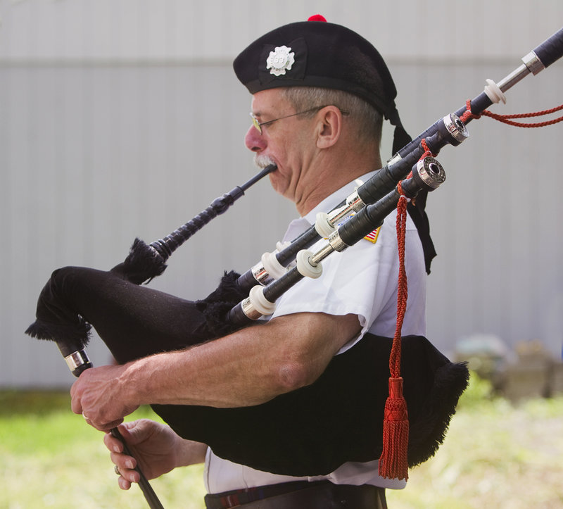 Rob Simmons, founder of the Guns 'N Hoses Pipes and Drums of Maine, plays the bagpipes at his Falmouth home on Saturday.