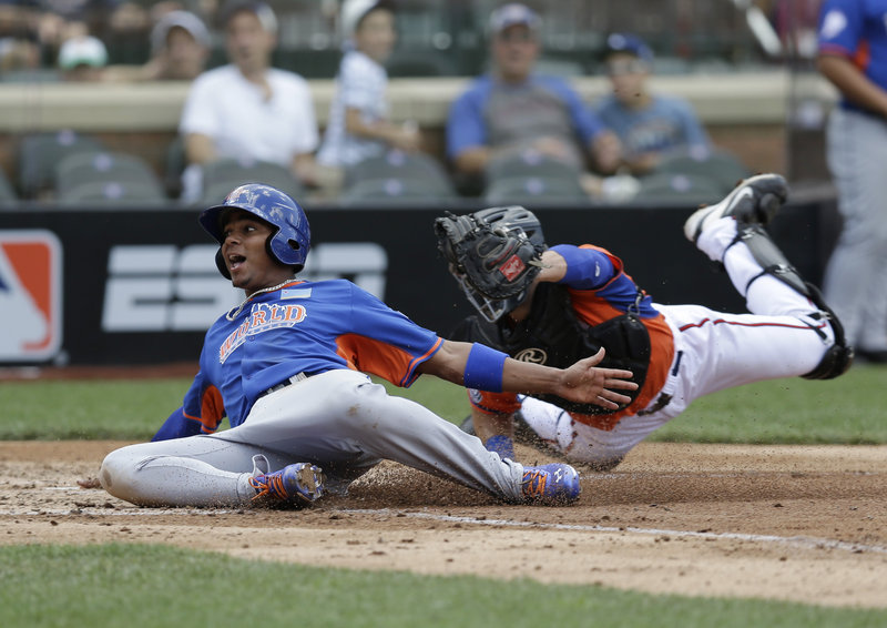 World's Xander Bogaerts, a former Portland Sea Dog, scores ahead of the tag by United States' Austin Hedges in the fourth inning of the All-Star Futures game Sunday. Bogaerts was 2 for 3 in the game, which the U.S. team won 4-2.