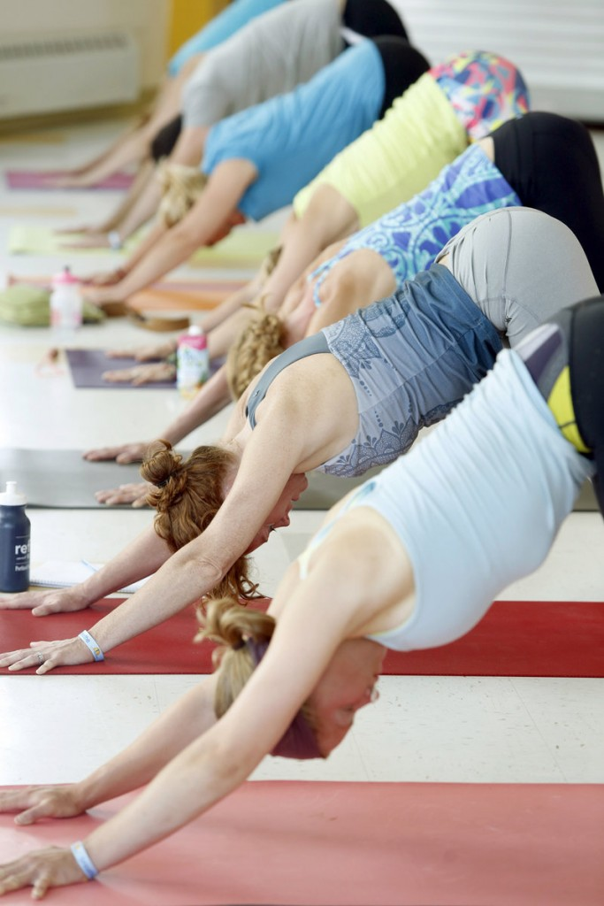 Students in the Yoga for Athletes class do a downward dog pose in unison.