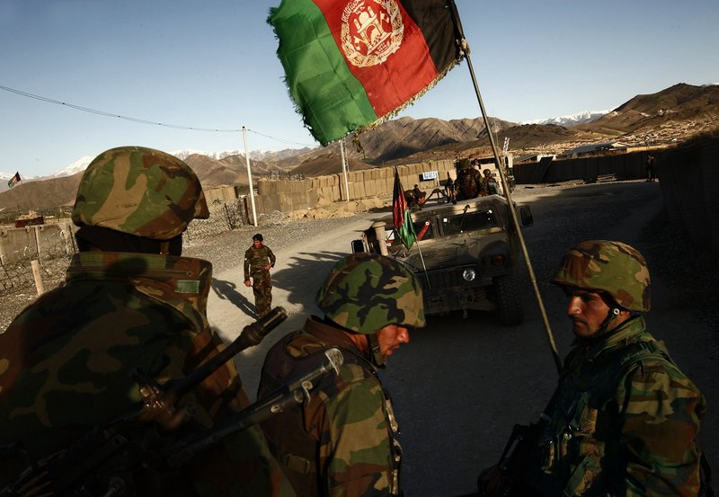 "Photos by Carolyn Cole/Los Angeles Times Afghan National Army soldiers prepare for patrol recently in Maidan Shar, a district in Wardak province. U.S. Army Lt. Col. Curby Scarborough says Afghan soldiers ""are at times more dependent on us than we'd like."""