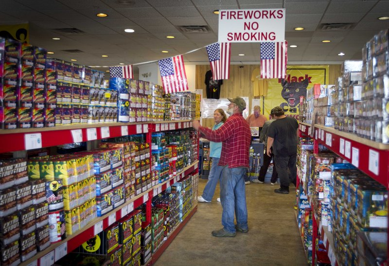 People shop for fireworks at the Pyro City retail store in Winslow on June 28. The government reported Monday that U.S. retail sales slowed in June.