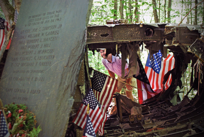 Forester Matt Miller, who grew up near what's now the Westover Air Reserve Base near Springfield, Mass., examines the remains of the B-52 that crashed into Elephant Mountain after departing from the then-Westover Air Force Base in 1963. Miller was just 4 years old at the time.