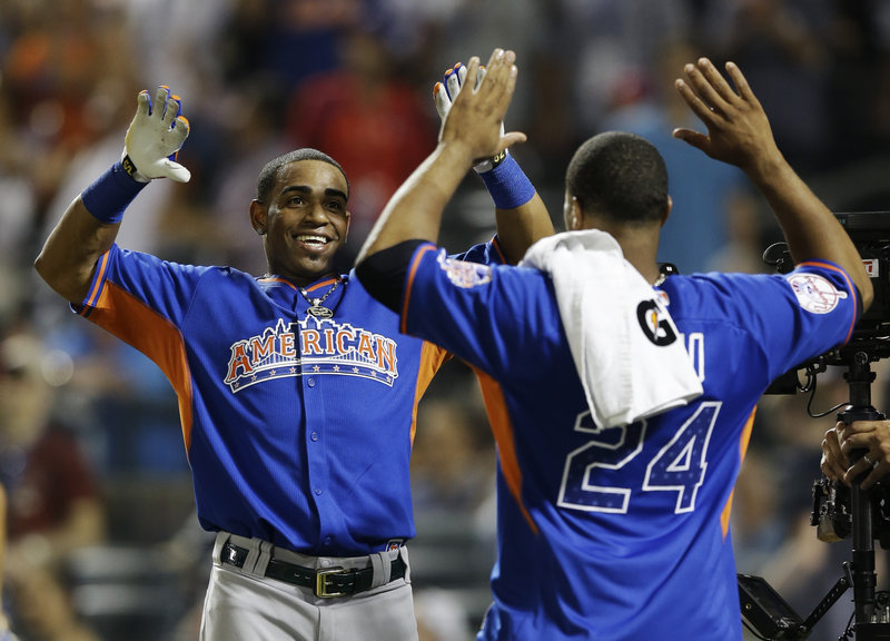 It's a double high-five for Yoenis Cespedes, left, as the Oakland Athletics slugger, celebrates with Robinson Cano after winning the MLB All-Star baseball Home Run Derby at Citi Field in New York City on Monday night.