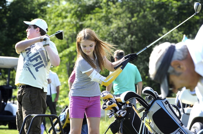 Keegan Moreau, a 14-year-old from Auburn, swings at a ball as instructors give lessons to handicapped golfers during their Monday sessions at Toddy Brook Golf Course in North Yarmouth. Moreau will head to Idaho to become a counselor at a camp for children with lost limbs.