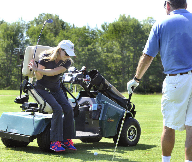 Monica Quimby of Scarborough hits the ball from an adaptive golf cart. Quimby, a paraplegic, is able to drive the car and adjust the swivel seat using hand controls.