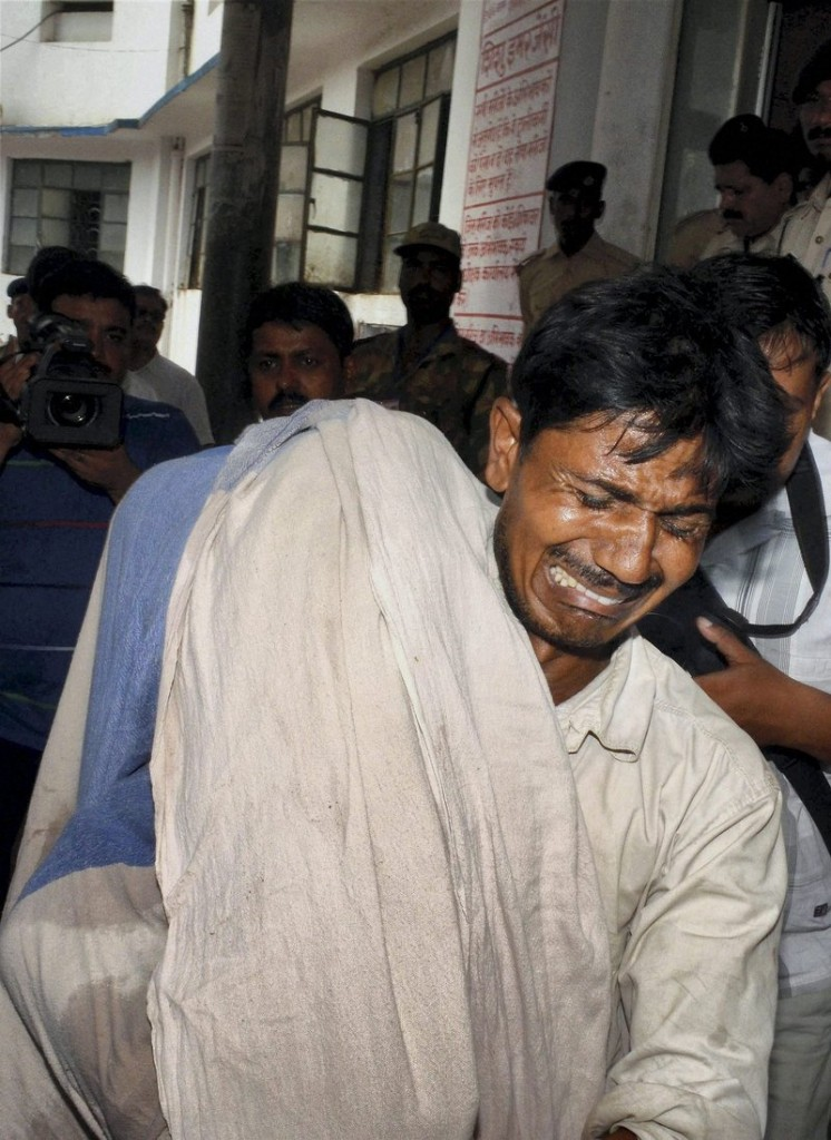 A distraught Indian man cries Wednesday while carrying the body of his daughter, one of 22 students who died after eating a free lunch at a school in Patna, India.