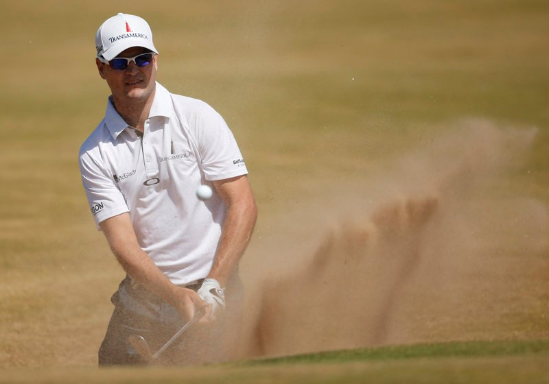 Zach Johnson knocks his ball out of a bunker Thursday during the first round of the British Open at Muirfield. Johnson grabbed the lead with a 5-under 66.