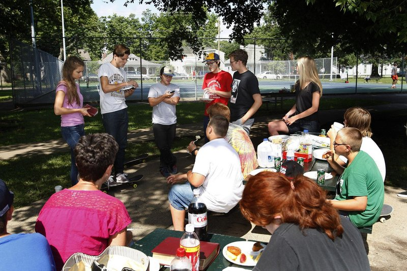 Gideon Maki, 20, second from left in background, reads a passage from Lamentations, in which Jeremiah talks about suffering, during a recent Skate Church service at the Skate Park in Woodland Park in Lexington, Ky.