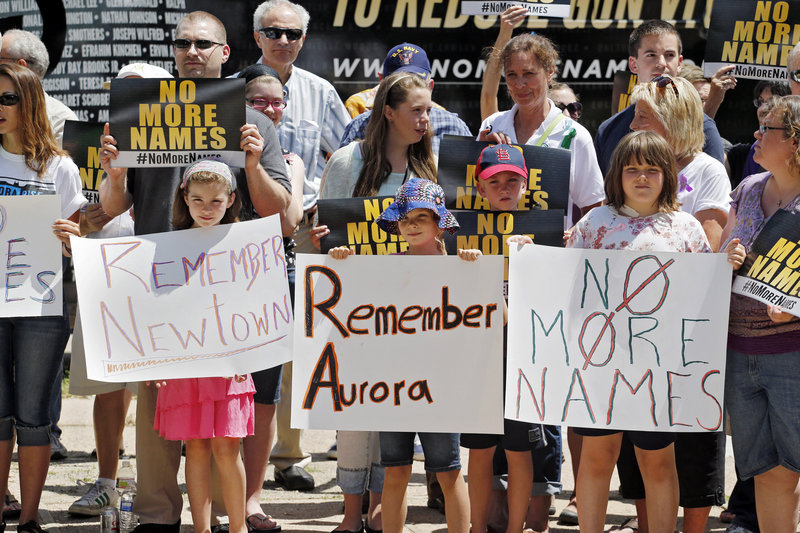 People hold signs as they gather for a remembrance rally for the Aurora theater shooting victims at Cherry Creek State Park in Aurora, Colo., on Friday. Saturday is the anniversary of the theater massacre where 12 people were killed and 70 wounded.