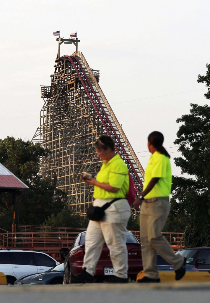 Six Flags Over Texas workers pass the Texas Giant roller coaster in Arlington, Texas, where a woman died Friday.