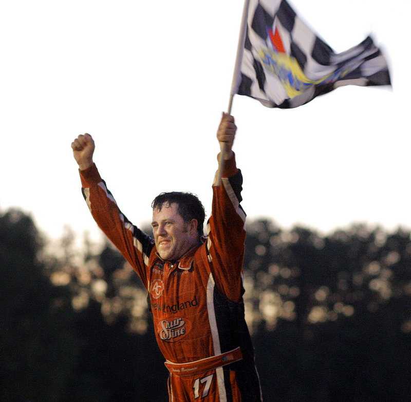 Travis Benjamin of Morrill is a happy driver as he waves the checkered flag after winning the 40th TD Bank 250 at Oxford Plains Speedway on Sunday.