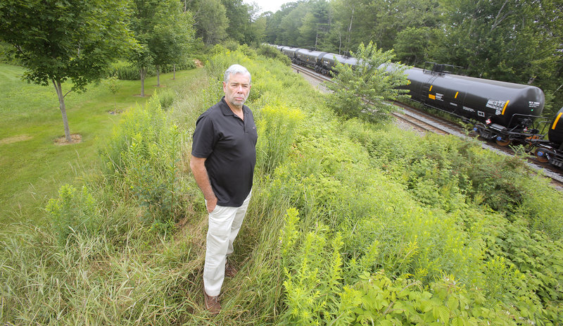 Bill Vinson is concerned about the frequency that tanker cars are being parked on a railroad siding next to his property in Scarborough. Vinson is photographed Monday, July 22, 2013 atop a berm between his backyard, at left, and the railroad tracks and siding.