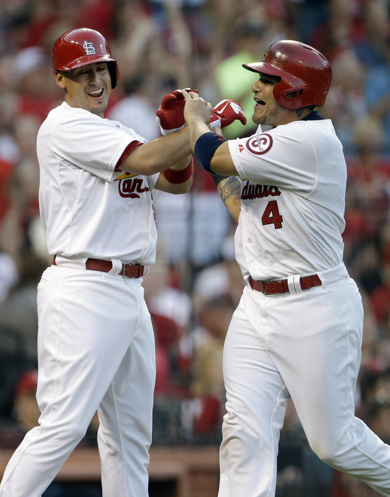 Allen Craig, left, and Yadier Molina celebrate after scoring on a hit during the Cardinals' win over the Phillies.