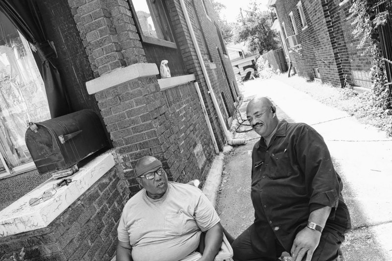 James Jackson, 65, left, and his friend Harry Jolliffi Sr., 63, sit in front of Jackson's home after patrolling their Jefferson-Chalmers neighborhood in Detroit on Friday.