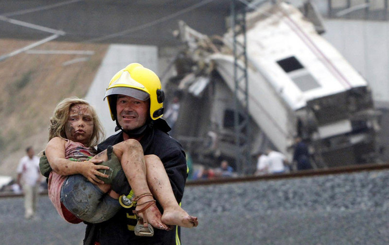 A firefighter carries an injured victim from the wreckage of a train crash near Santiago de Compostela in northwestern Spain. Witnesses said a fire, probably burning diesel fuel, engulfed passengers trapped in at least one of the rail cars.