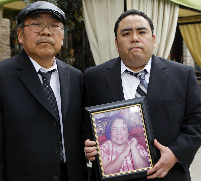 "Accompanied by Peter Uno, his father, left, Jeffrey Uno holds a photo of his mother, Noriko Uno, who died in an alleged ""sudden unintended acceleration"" crash in a Toyota Camry in August 2009. The case is a bellwether for Toyota."