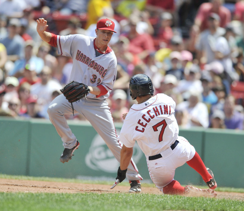 Garin Cecchini of the Sea Dogs slides across the plate as Harrisburg pitcher Richie Mirowski slips out of the way in the seventh inning.