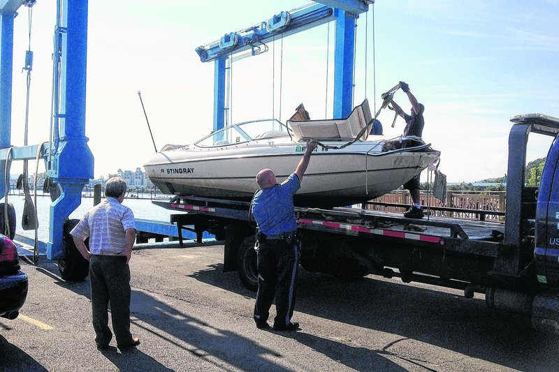 Police load a 21-foot powerboat onto a trailer in Piermont, N.Y., Saturday, after it struck a barge Friday night.