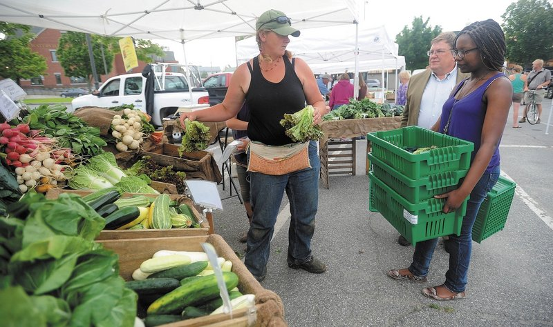 Hanne Teirney of Cornerstone and Fail Better Farms offers fresh organic produce to Noma Moyo, 21, a Colby College junior, and Joe Klaus, food services manager at Colby College, at the Waterville Farmers Market on Thursday.