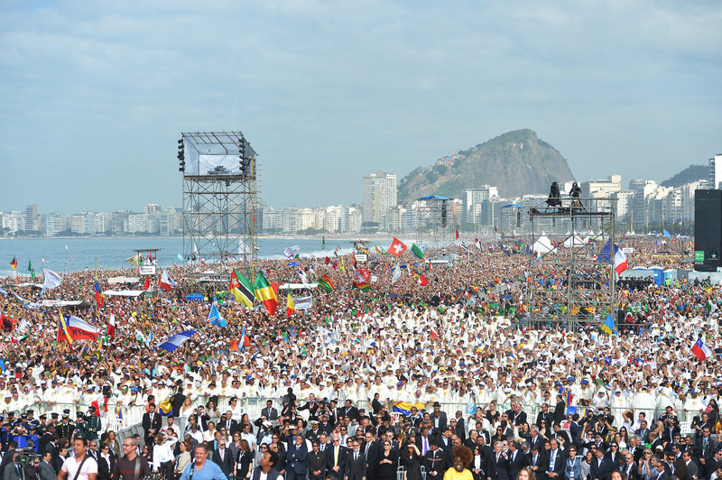 Crowds wait for the arrival of Pope Francis to celebrate Mass on Copacabana beach in Rio de Janeiro, Brazil, on Sunday. The pontiff wrapped up his historic trip to his home continent by urging young people to go out and spread their faith.