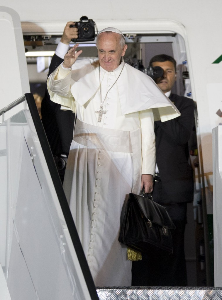 Pope Francis waves as he boards his plane at the airport in Rio de Janeiro on Sunday after a weeklong visit to Brazil.