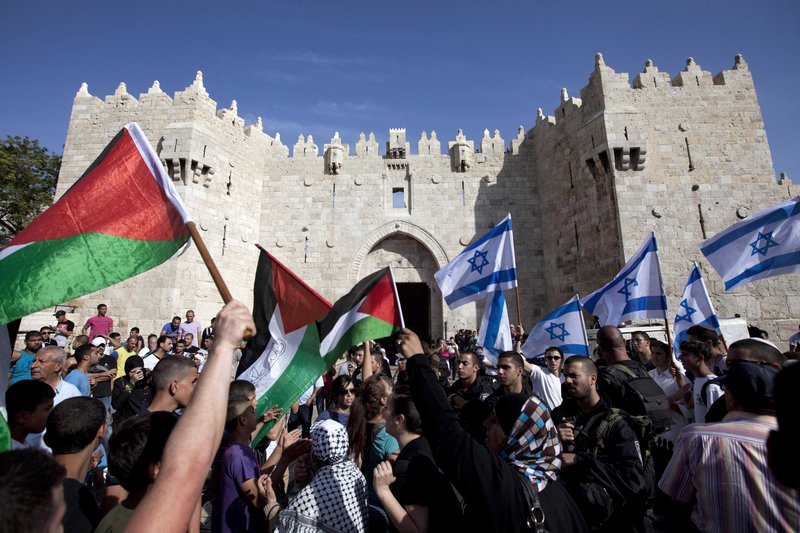 Israelis and Palestinians wave flags as Israelis celebrate Jerusalem Day in Jerusalem's old city May 8. The U.S. on Sunday announced the resumption of Israeli-Palestinian talks.