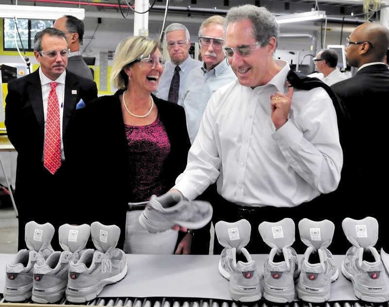 Trade Representative Michael Froman, right, examines a sneaker in front of some of Maine's elected officials and New Balance company officials at the production plant in Norridgewock on Monday.