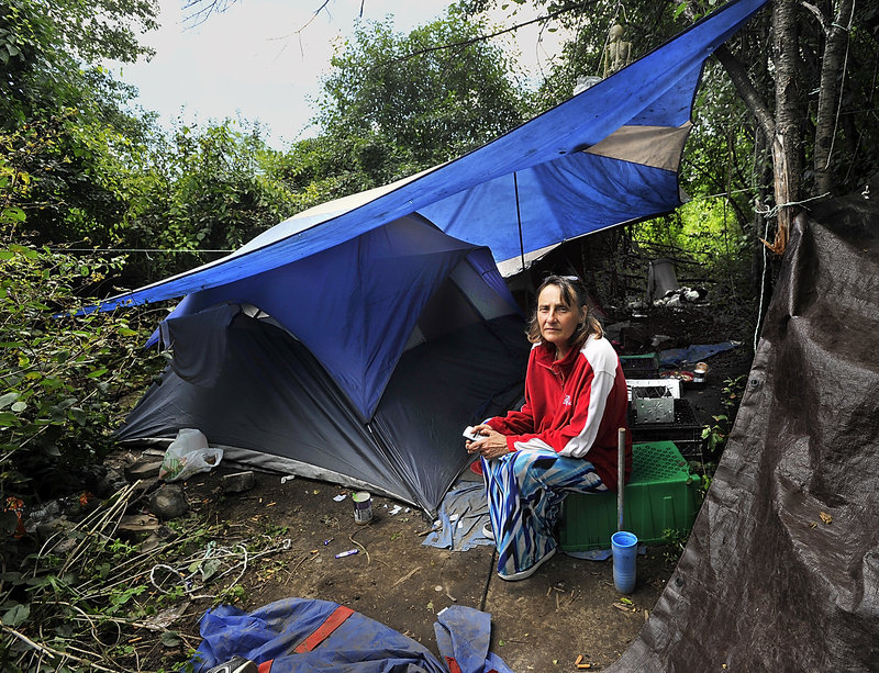 Anne M. Blake and life partner Kevin McBride have filed a lawsuit against the Westbrook Police Department saying they were illegally evicted from their apartment. In this Tuesday, July 30, 2013 photo she sits at a camp, which they built and now live in, near the Maine Turnpike at Exit 8.