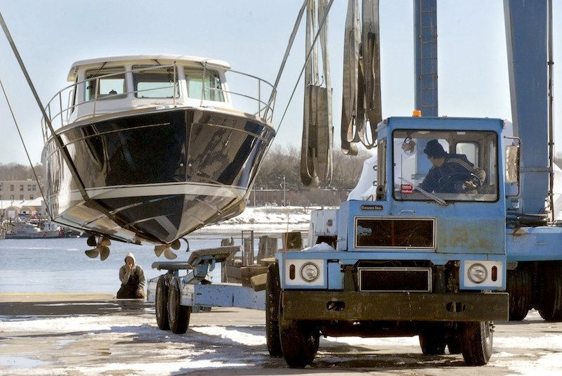"""In this March 2009 file photo, workers guide a trailer under a 38-foot Sabre """"Express"""" from a travel lift at Gowen Marine in Portland. Gowen Marine has been sold to Phineas Sprague, the latest development in a serious of moving parts on the city's waterfront."""